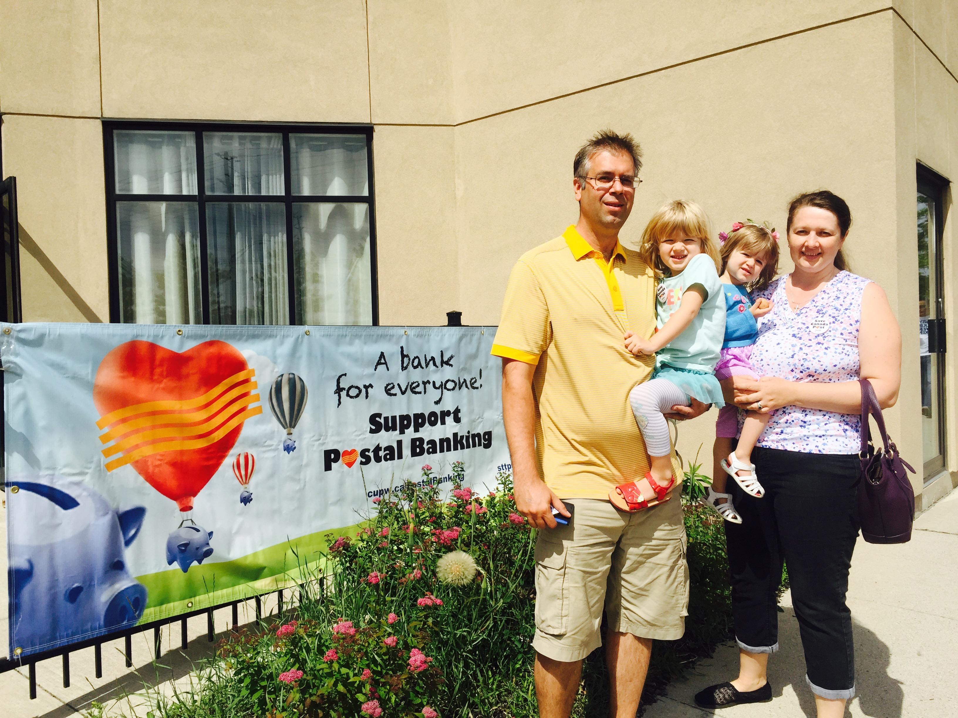 Couple travaillant au centre principal d'acheminement de Toronto et ses deux enfants debout près d'une bannière « Une banque postale, une banque pour tous! ».