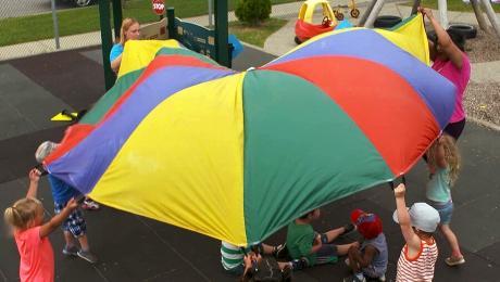 Des enfants et des éducatrices s'amusent avec un parachute multicolore dans l'aire de jeu d'une garderie.