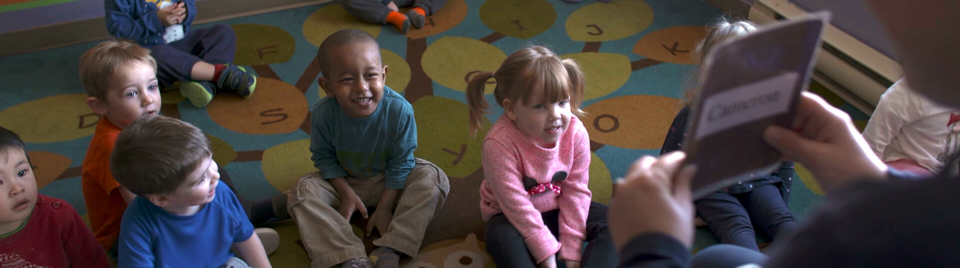 Children sitting on a carpet during circle time at a day care.