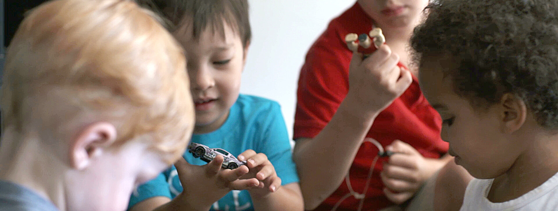 A child plays with a toy car as other children look on.