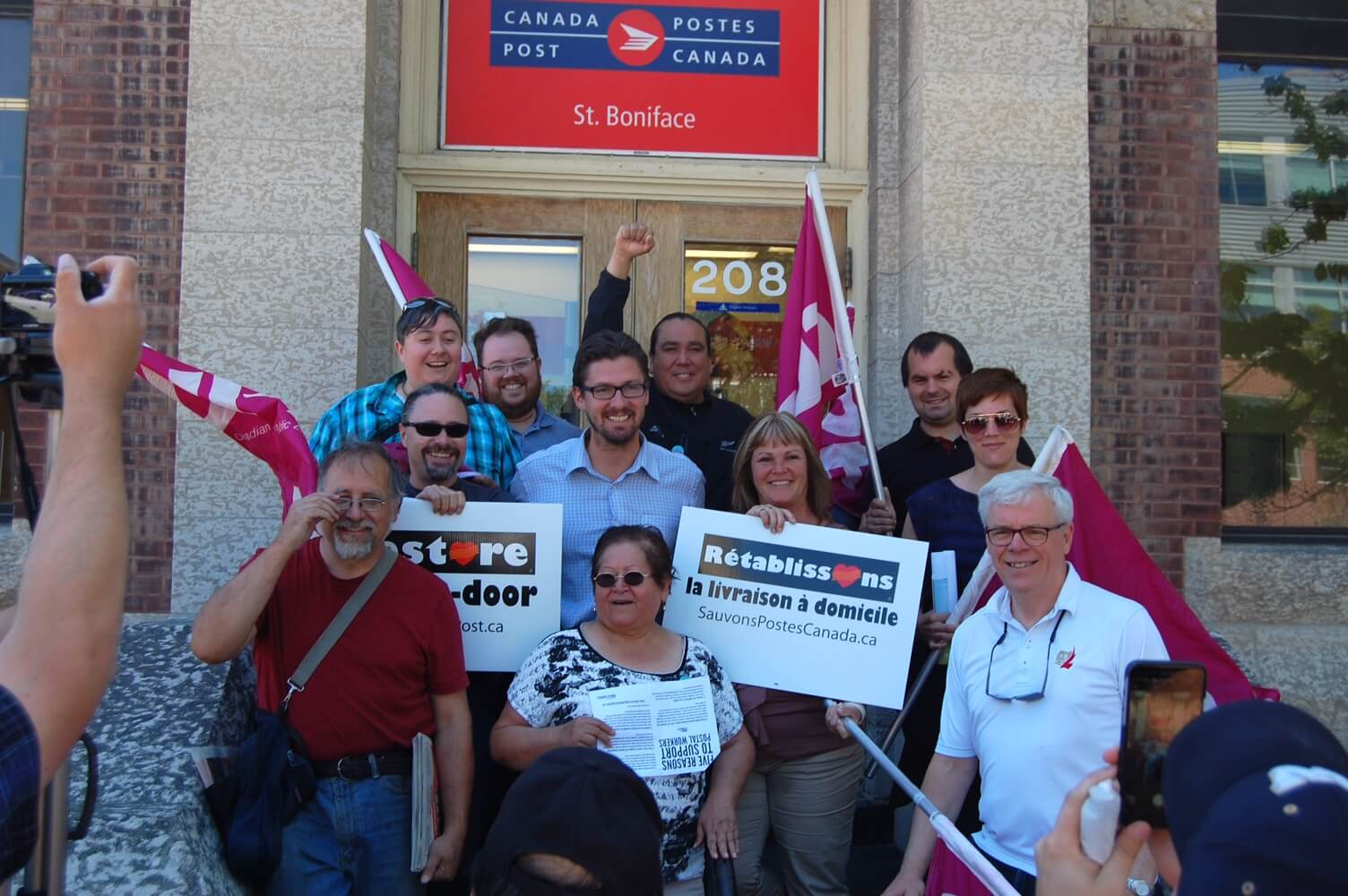 "Group photo of people in front of St. Boniface post office with ""Restore Door-to-Door"" signs"